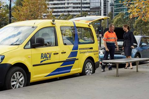 RACV Roadside Assistance Mechanic stands in front of a RACV vehicle