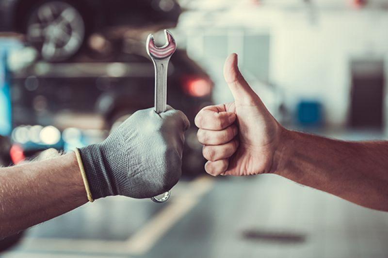 Mechanic holds tool and another man gives thumbs up