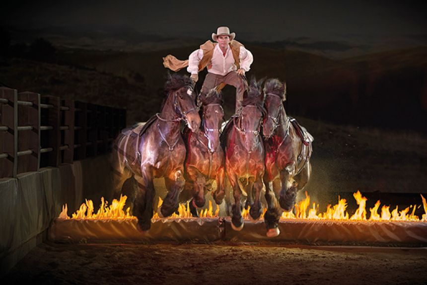 Man standing on horses over flames