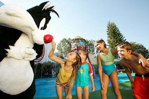 Children boop Sylvester the cat on the nose at a theme park
