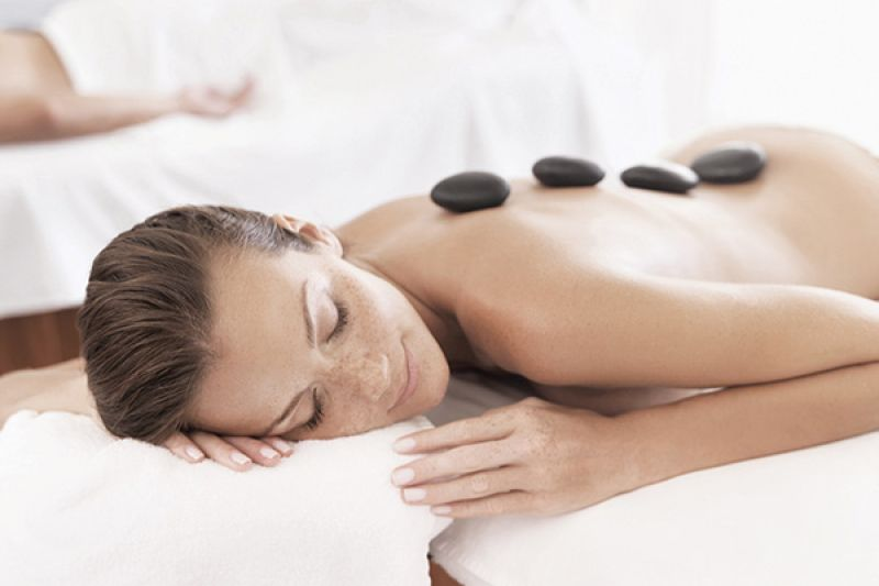 Woman lying face down on massage bed with rocks on back