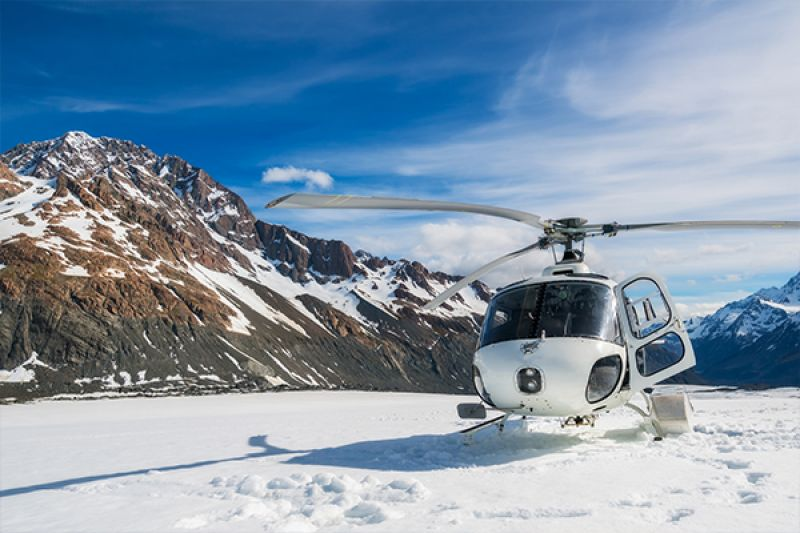 helicopter landing on top of an mountain covered in snow in new zealand