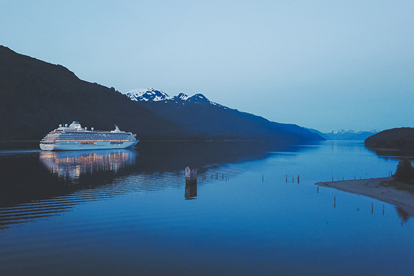 cruise ship sailing alond a stretch of water at dusk