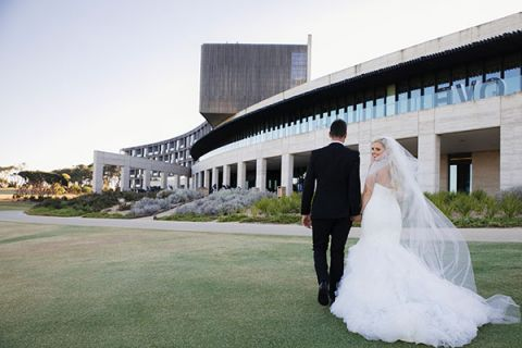 A bride and groom walk along a pier at sunset at RACV Torquay Resort